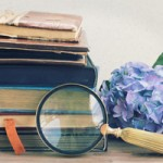 old books with flowers and looking glass